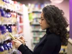Woman consulting shopping list in grocery store