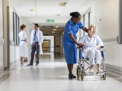 Patient in wheelchair talking to a nurse in the hall of a hospital