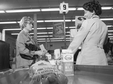 A shopper uses food stamps at a grocery store in March 1970