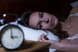 Woman lying in bed staring at the clock