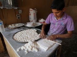 A boy makes pastry at a shop in Darkush town, Idlib countryside, Syria, May 26, 2013