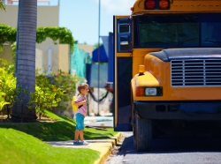 A young boy waits to get on the school bus