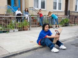 Kid with skateboard sitting on the curb with friends and family in the background