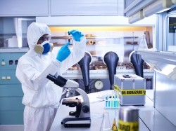 Scientist working in a laboratory wearing a protective suit