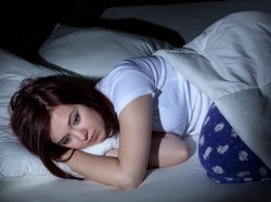 woman with insomnia wearing blue pajama bottoms