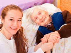 Young doctor holding elderly woman