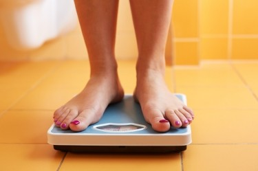 A woman stands on a bathroom scale