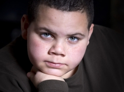 handsome,teen,teenage,young,boy,male,portrait,resting,head,on,hand,latino,hispanic,african american,one,persone,alone,vignette,intense,intensity,staring,at camera,looking,serious,concentrating,concentration