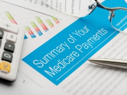 Medicare payments summary on top of other paperwork, with glasses and calculator
