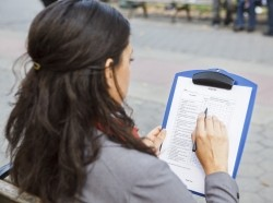 Woman sits on park bench filling out survey, photo by DW labs Incorporated/Adobe Stock