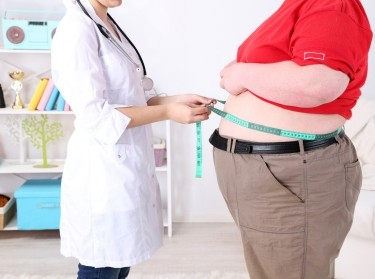 doctor measuring an obese patient's waist