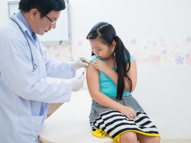 Doctor vaccinating little girl
