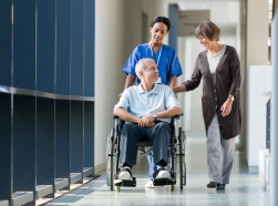 Orderly pushing man in wheelchair down hospital hall