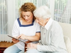 Caregiver and elderly woman looking at a tablet computer