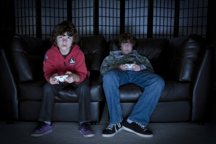 Two boys sitting on a couch playing video games, photo by Sean Davis/Fotolia