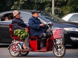An elderly couple carrying vegetables ride a tricycle along a street in Beijing, October 17, 2013