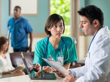Nurse talking to doctor about patient in busy waiting room