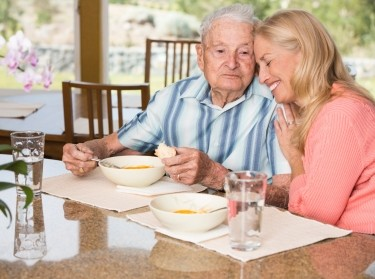 Senior man and adult daughter enjoying time together over lunch