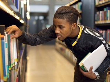 Young student looking for reference books at high school library