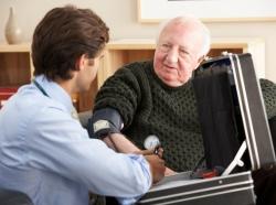 Doctor taking senior man's blood pressure at home