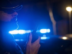 Police officer radioing for backup, photo by karrastock/Adobe Stock