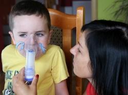 A woman helps a boy use a nebulizer