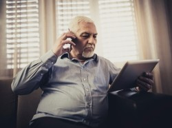 Older man using a cell phone and iPad