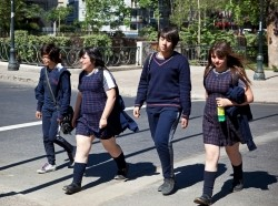 Santiago, Chile - November 14, 2011: Young woman students of high school walking down a street from school in Santiago de Chile. They wearing their blue school uniform.