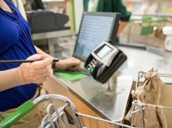 Woman using credit card machine at grocery store check out