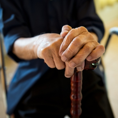 An elderly man's hands clasped on a cane