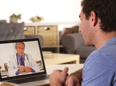 A young man uses a laptop to talk to a doctor