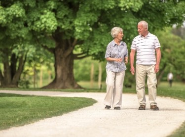 Two older adults walking in a park