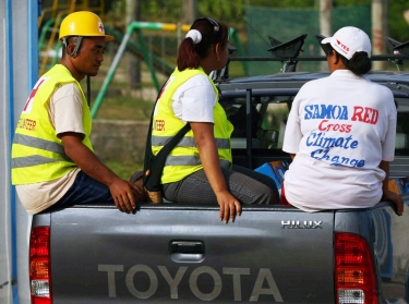 Red Cross members travel in a truck to a water station following an earthquake in Lalomanu, Samoa