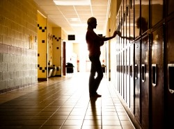 Silhouette of a high school student standing in a hallway by lockers