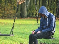 Teenage boy sitting on a swing, smoking
