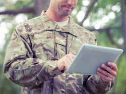 A soldier using a tablet outside