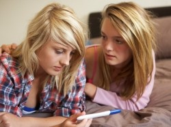 Two teenage girls lying on a bed looking at a pregnancy test