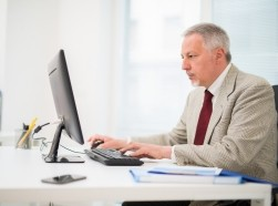 An older man in a suit working on a computer