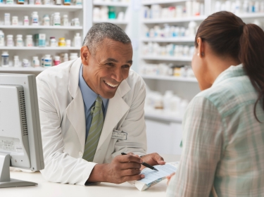 Pharmacist discussing prescription with customer