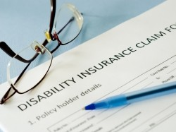 A disability insurance claim form with a pen and reading glasses