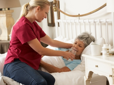 Health worker giving an elderly woman a glass of water in bed