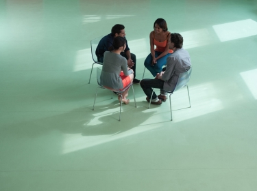Four people sitting in a circle talking
