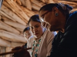 A senior Native American woman demonstrates weaving to two young women, photo by Hoptocopter / Getty Images