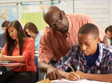 African American teacher helping high school student in the classroom