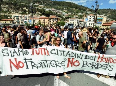 Protesters hold a banner reading 'We are all citizens of the world, no frontier, no borders' in Ventimiglia, Italy, August 7, 2016