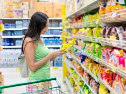 Woman looking at a bag of potato chips in the supermarket