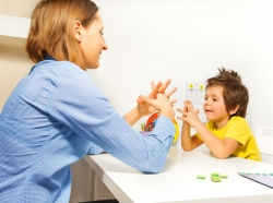 Teacher working with young boy at a table