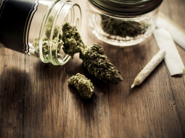 Recreational marijuana buds in glass jars next to a joint and rolling papers