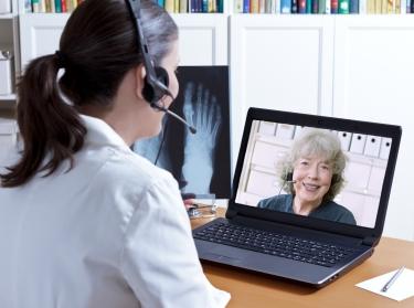 Woman talks to doctor using telemedicine
