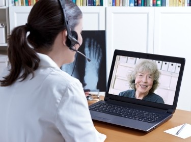 Woman talks to doctor using telemedicine